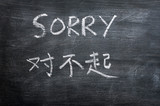 Sorry - word written on a smudged blackboard poster
