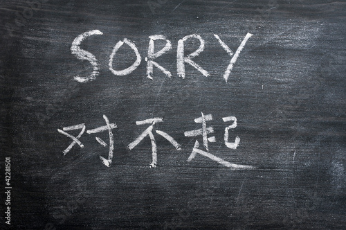 Sorry - word written on a smudged blackboard
