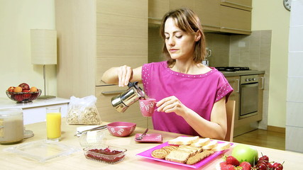Attractive woman in pajamas having breakfast at home