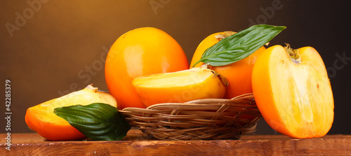Appetizing persimmons in pad on wooden