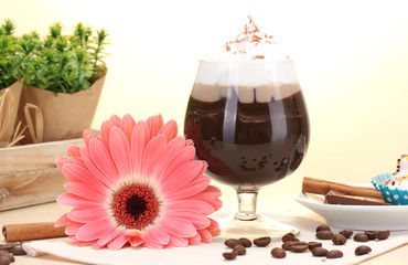 glass of coffee cocktail and gerbera flower on wooden table