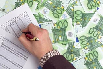 Hombre de negocios revisando las ganancias en un fondo de billet