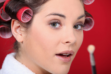 Portrait of woman with curlers and brush in hand