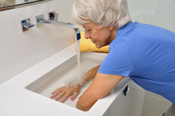 Seniorin macht Wechselbäder im Waschbecken