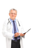 A mature healthcare professional holding a clipboard and posing