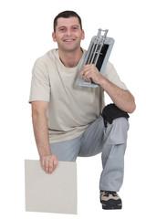 Man kneeling with tile cutter
