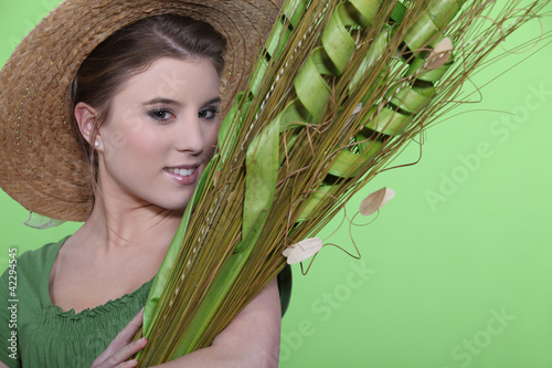 Woman in hat holding large leaves