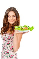 Girl holding a plate with salad, isolated on white