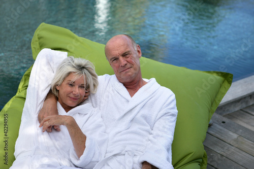 Elderly couple lying on inflatable mattress on a pool deck