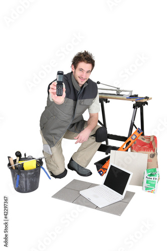 young craftsman with laptop showing phone