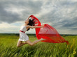 Brunette girl jumping with red fabric in summer day