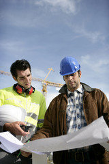 Tradesman and an engineer examining a blueprint