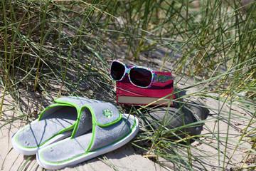 Bunte Sonnenbrille liegt auf Buch in den Dünen