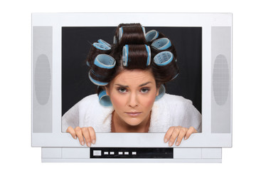 Woman in hair rollers trapped in television
