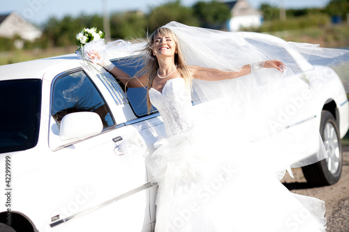 young bride standing beside a limousine