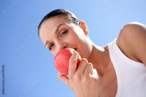 Brunette biting into red apple