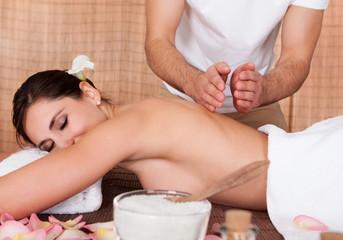 Beautiful young woman getting back massage