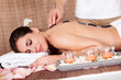 Beautiful young woman getting hot stone therapy