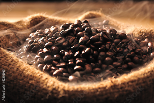 Fototapeta Coffee beans with smoke in burlap sack
