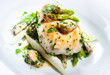 Delicious dish with fish fillet, asparagus and herbs on a plate