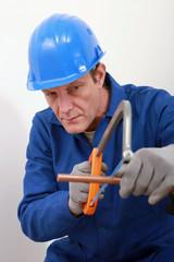 A tradesman using a saw to cut a copper tube