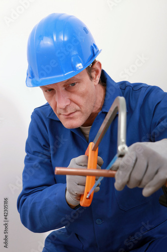 A tradesman using a saw to cut a copper tube