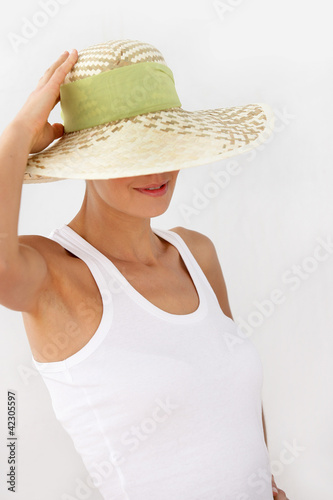 Shy woman pushing hat over face