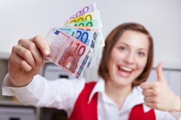 Frau mit Geldscheinen hält Daumen hoch