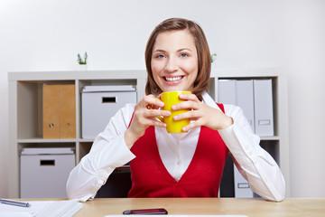 Lächelnde Frau trinkt Kaffee im Büro