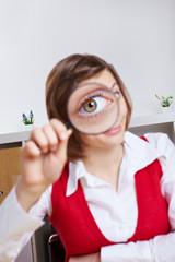 Geschäftsfrau schaut durch Lupe