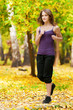 A young girl running in autumn park