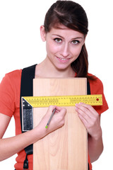Woman measuring width of laminate flooring