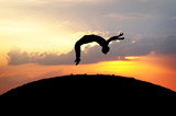 silhouette of gymnast jumping on hill in sunset