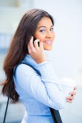 junge frau läuft telefonierend durch die stadt