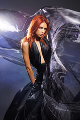 Fashion shoot of a young redhead woman in a beautiful dress