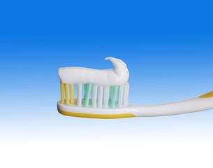 Zahnpasta auf Zahnbürste vor blauem Fond