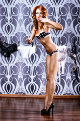A young and sexy redhead woman posing in erotic lingerie