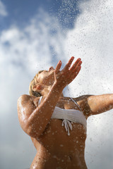 Woman splashing water on herself