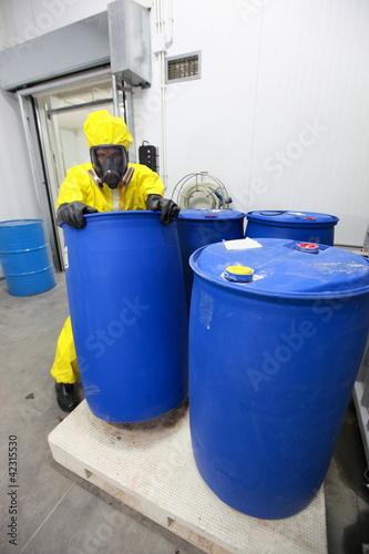 worker in uniform dealing with barrels of hazardous substance