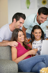 Two couples at home laughing at a laptop