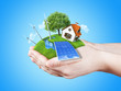 Hands holding clear green meadow alternative energy concept