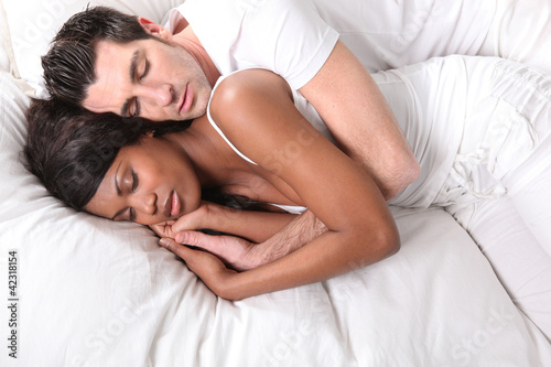 Young couple asleep in bed together