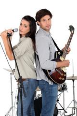 Woman singing whilst man plays guitar