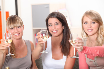 Three women toasting with glass of wine