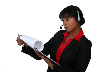 black businesswoman with headset holding clipboard