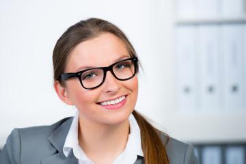 hübsche junge frau mit brille im büro