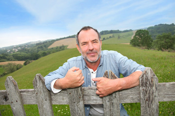 Portrait of smiling farmer leaning on fence
