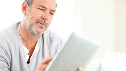 Senior man using electronic tablet