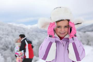 Little girl in snow near parents