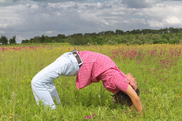 Man exercises in the summer meadow